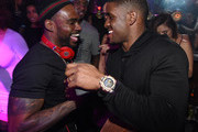 """DJ Stevie J (L) greets running back Reggie Bush of the Detroit Lions at """"LIV on Sundays"""" presented by TAO Takeover Party at CAKE Nightclub on February 1, 2015 in Scottsdale, Arizona."""