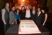 """Actors Owain Yeoman, Tim Kang, CBS President Nina Tassler, Amanda Righetti, Director Bruno Heller, Simon Baker, Warner Bros. President Peter Roth, and actress Robin Tunney participate in the cutting of cake at the CBS 100 episode celebration of """"The Mentalist"""" held at The Edison on October 13, 2012 in Los Angeles, California."""