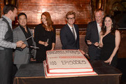 """(L-R) Actors Owain Yeoman, Tim Kang, Amanda Righetti, Simon Baker, Director Bruno Heller, and actress Robin Tunney participate in the cutting of cake at the CBS 100 episode celebration of """"The Mentalist"""" held at The Edison on October 13, 2012 in Los Angeles, California."""