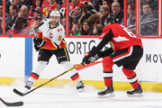Mark Giordano #5 of the Calgary Flames tips the puck past Mark Stone #61 of the Ottawa Senators in the first period at Canadian Tire Centre on March 9, 2018 in Ottawa, Ontario, Canada.