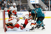 Mike Smith #41 and Travis Hamonic #24 of the Calgary Flames stop Rourke Chartier #60 of the San Jose Sharks from scoring during their preseason game at SAP Center on September 27, 2018 in San Jose, California.