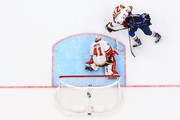 Austin Czarnik #27 and Mike Smith #41 of the Calgary Flames defend the goal against Tyler Bozak #21 of the St. Louis Blues at the Enterprise Center on October 11, 2018 in St. Louis, Missouri.