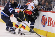 TJ Galiardi #21 of the Winnipeg Jets gets past Ladislav Smid #15 of the Calgary Flames and Michael Frolik #67 for the puck in second period action in an NHL game at the MTS Centre on October 19, 2014 in Winnipeg, Manitoba, Canada.