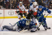 Goalie Jacob Markstrom #25 of the Vancouver Canucks looks to cover up the loose puck while James Neal #18 of the Calgary Flames and Chris Tanev #8 of the  Canucks battle in NHL action on October, 3, 2018 at Rogers Arena in Vancouver, British Columbia, Canada.