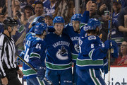 Jake Virtanen #18 of the Vancouver Canucks is congratulated by teammates Tyler Motte #64, Brandon Sutter #20 and Chris Tanev #8 after scoring a goal against the Calgary Flames in NHL action on October, 3, 2018 at Rogers Arena in Vancouver, British Columbia, Canada.