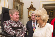 Samuel Bailey (16) meets Camilla, Duchess of Cornwall during a reception at Clarence House hosted by the Duchess of Cornwall, for youngsters and their carers from Helen and Douglas House on December 11, 2013 in London, England.