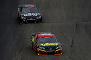 Clint Bowyer, driver of the #15 5-hour ENERGY Toyota, leads Martin Truex Jr., driver of the #78 Furniture Row Chevrolet, during the NASCAR Sprint Cup Series Camping World RV Sales 301 at New Hampshire Motor Speedway on July 13, 2014 in Loudon, New Hampshire.