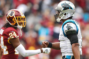 Quarterback Cam Newton #1 of the Carolina Panthers walks off the field past cornerback Josh Norman #24 of the Washington Redskins after turning the ball over on downs during the fourth quarter at FedExField on October 14, 2018 in Landover, Maryland.