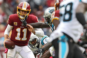 Quarterback Alex Smith #11 of the Washington Redskins is hit in the face mask against the Carolina Panthers during the first half at FedExField on October 14, 2018 in Landover, Maryland.