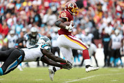 Adrian Peterson #26 of the Washington Redskins runs past Mario Addison #97 of the Carolina Panthers during the second half at FedExField on October 14, 2018 in Landover, Maryland.