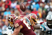 Alex Smith #11 of the Washington Redskins fumbles the ball after being hit by Julius Peppers #90 of the Carolina Panthers during the fourth quarter at FedExField on October 14, 2018 in Landover, Maryland.