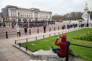 A woman watches the Changing of the Guard ceremony outside Buckingham Palace on the day that Queen Elizabeth II is set to move to Windsor Palace in a bid to avoid the COVID-19 coronavirus pandemic on March 18, 2020 in London, England.