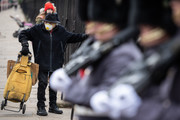 A man wearing a face mask watches as members of the Coldstream Guards take begin the Changing of the Guard ceremony at Buckingham Palace on the day that Queen Elizabeth II is set to move to Windsor Palace in a bid to avoid the COVID-19 coronavirus pandemic on March 18, 2020 in London, England.