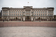 A handful of pedestrians and tourists walk past Buckingham Palace on the day that Queen Elizabeth II is set to move to Windsor Palace in a bid to avoid the COVID-19 coronavirus pandemic on March 18, 2020 in London, England.