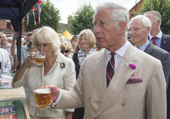 Charles, Duke of Cornwall and Camilla, Duchess of Cornwall try a taste of Rutland Bitter as they meets members of the local community and business owners on July 28, 2014 in Oakham, England. The Prince of Wales, as Patron of  'Step Up To Serve' met local young people involved in the campaign before visiting Oakham Castle, where The Duchess of Cornwall presented a decorative horse shoe to mark her first official visit to the town.