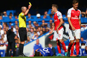 Calum Chambers of Arsenal is shown a yellow card by referee Mike Dean during the Barclays Premier League match between Chelsea and Arsenal at Stamford Bridge on September 19, 2015 in London, United Kingdom.