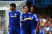 Oscar of Chelsea celebrates with teammates Diego Costa (L) and Willian (R) of Chelsea after scoring the opening goal during the Barclays Premier League match between Chelsea and Aston Villa at Stamford Bridge on September 27, 2014 in London, England.