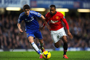 Patrice Evra of Manchester United is challenged by Oscar of Chelsea during the Barclays Premier League match between Chelsea and Manchester United at Stamford Bridge on January 19, 2014 in London, England.