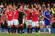 Referee Mike Dean is surrounded by Radamel Falcao García, Ander Herrera and Wayne Rooney of Manchester United during the Barclays Premier League match between Chelsea and Manchester United at Stamford Bridge on April 18, 2015 in London, England.