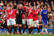 Referee Mike Dean is surrounded by Radamel Falcao García, Marouane Fellaini , Ander Herrera and Wayne Rooney of Manchester United during the Barclays Premier League match between Chelsea and Manchester United at Stamford Bridge on April 18, 2015 in London, England.