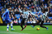 (L-R) Eden Hazard of Chelsea is tackled by Mapou Yanga-Mbiwa and Vurnon Anita of Newcastle United during the Barclays Premier League match between Cheslea and Newcastle United at Stamford Bridge on February 8, 2014 in London, England.