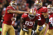 Vernon Davis #85 is congratulated by Colin Kaepernick #7 and Alex Boone #75 of the San Francisco 49ers after catching a touchdown pass in the first quarter against the Chicago Bears at Candlestick Park on November 19, 2012 in San Francisco, California.
