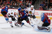 Jonathan Toews #19 of the Chicago Blackhawks takes a shot on goalie Calvin Pickard #31 of the Colorado Avalanche as Jan Hejda #8 of the Colorado Avalanche defends at Pepsi Center on December 27, 2014 in Denver, Colorado. The Blackhawks defeated the Avalanche 5-2.