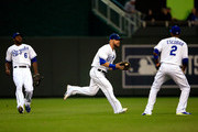 Alex Gordon #4 of the Kansas City Royals makes a running catch in shallow center field as Lorenzo Cain #6 and Alcides Escobar #2 watch during the 1st inning of the game against the Chicago White Sox at Kauffman Stadium on September 15, 2014 in Kansas City, Missouri.