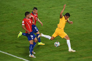 Tim Cahill of Australia is tripped up after a challenge by Gonzalo Jara (L) and Gary Medel of Chile (C) during the 2014 FIFA World Cup Brazil Group B match between Chile and Australia at Arena Pantanal on June 13, 2014 in Cuiaba, Brazil.