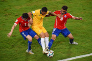 Tim Cahill of Australia fights off challenges by Eugenio Mena (L) and Gonzalo Jara of Chile during the 2014 FIFA World Cup Brazil Group B match between Chile and Australia at Arena Pantanal on June 13, 2014 in Cuiaba, Brazil.