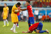 Tim Cahill of Australia stands over Gonzalo Jara of Chile (grounded) as Charles Aranguiz of Chile intervenes during the 2014 FIFA World Cup Brazil Group B match between Chile and Australia at Arena Pantanal on June 13, 2014 in Cuiaba, Brazil.