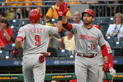 Jose Peraza #9 of the Cincinnati Reds is greeted at home plate by Joey Votto #19 after hitting a solo home run in the first inning during the game against the Pittsburgh Pirates at PNC Park on September 5, 2018 in Pittsburgh, Pennsylvania.