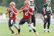 Quarterbacks Johnny Manziel #2 and Connor Shaw #9 pass the ball during training camp at the Cleveland Browns training facility on July 26, 2014 in Berea, Ohio.