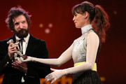 """Director Fabio D'Innocenzo receives the Silver Bear for Best Screenplay for the film """"Bad Tales"""" from Member of the International Jury Berenice Bejo on stage at the closing ceremony of the 70th Berlinale International Film Festival Berlin at Berlinale Palace on February 29, 2020 in Berlin, Germany."""