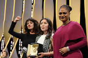Asia Argento raises her arm (L) as actress Samal Yeslyamova receives the receives the Best Actress award for 'Ayka' (The Little One) as Jury member Ava DuVernay (R) presents on stage during the Closing Ceremony at the 71st annual Cannes Film Festival at Palais des Festivals on May 19, 2018 in Cannes, France.