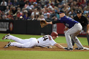 Paul Goldschmidt #44 of the Arizona Diamondbacks dives back to first base as Justin Morneau #33 of the Colorado Rockies reaches for the ball during the first inning at Chase Field on September 29, 2015 in Phoenix, Arizona.