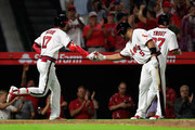 Shohei Ohtani #17 is congratulated by Albert Pujols #5 and Mike Trout #27 of the Los Angeles Angels of Anaheim after hitting a three-run homerun during the fourth inning of a game against the Colorado Rockies at Angel Stadium on August 27, 2018 in Anaheim, California.