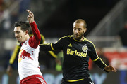 Sacha Kljestan #16 of New York Red Bulls trips over Federico Higuain #10 of Columbus Crew during their match at Red Bull Arena on November 29, 2015 in Harrison, New Jersey.