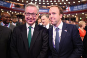 """Secretary of State for Environment, Food and Rural Affairs Michael Gove and Secretary of State for Health and Social Care Matt Hancock (R) take their seats ahead of British Prime Minister Theresa May's speech on the final day of the Conservative Party Conference at The International Convention Centre on October 3, 2018 in Birmingham, England. British Prime Minister Theresa May will deliver her leader's speech to the 2018 Conservative Party Conference today. Appealing to the """"decent, moderate and patriotic"""", she will state that the Conservative Party is for everyone who is willing to """"work hard and do their best"""". This year's conference took place six months before the UK is due to leave the European Union, with divisions on how Brexit should be implemented apparent throughout."""