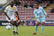 Jordan Clarke of Coventry City plays the ball watched by Jabo Ibehre of Colchester United during the Sky Bet League One match between Coventry City and Colchester United at Sixfields Stadium on September 8, 2013 in Northampton, England.