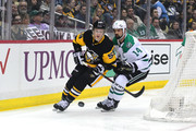 Jake Guentzel #59 of the Pittsburgh Penguins brings the puck out from behind the net against Jamie Benn #14 of the Dallas Stars at PPG PAINTS Arena on March 11, 2018 in Pittsburgh, Pennsylvania.