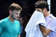 Switzerland's Roger Federer (R) and Belgium's David Goffin (L) pass each as they change ends between games during their men's singles semi-final match on day seven of the ATP World Tour Finals tennis tournament at the O2 Arena in London on November 18, 2017. / AFP PHOTO / Glyn KIRK