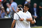 Novak Djokovic of Serbia embraces Roger Federer of Switzerland at the net following victory in his Men's Singles final during Day thirteen of The Championships - Wimbledon 2019 at All England Lawn Tennis and Croquet Club on July 14, 2019 in London, England.
