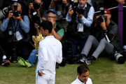 Novak Djokovic of Serbia holds the trophy as Roger Federer of Switzerland walks past after winning his Men's Singles final against Roger Federer of Switzerland during Day thirteen of The Championships - Wimbledon 2019 at All England Lawn Tennis and Croquet Club on July 14, 2019 in London, England.
