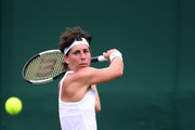 Carla Suarez Navarro of Spain plays a shot in her Ladies' Singles first round match against Samantha Stosur of Australia during Day two of The Championships - Wimbledon 2019 at All England Lawn Tennis and Croquet Club on July 02, 2019 in London, England.