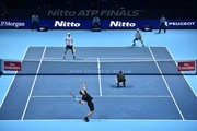 Britain's Jamie Murray (bottom L) serves over his partner Brazil's Bruno Soares (bottom R) during their men's doubles match against USA's Bob Bryan (top L) and USA's Mike Bryan (top R) on day two of the ATP World Tour Finals tennis tournament at the O2 Arena in London on November 13, 2017. / AFP PHOTO / Glyn KIRK