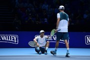 USA's Mike Bryan (R) goes to help up USA's Bob Bryan (L) during their men's doubles match against Britain's Jamie Murray and Brazil's Bruno Soares on day two of the ATP World Tour Finals tennis tournament at the O2 Arena in London on November 13, 2017. / AFP PHOTO / Glyn KIRK