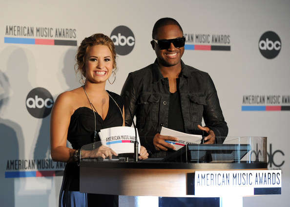 Demi Lovato Recording artists Demi Lovato (L) and Taio Cruz speak at the 2010 American Music Awards Nominations Press Conference held at The Mixing Room at the JW Marriott Los Angeles at L.A. LIVE on October 12, 2010 in Los Angeles, California.