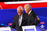 Sen. Bernie Sanders (I-VT) (L) and former Vice President Joe Biden put their arms around each other during the Democratic Presidential Debate at Otterbein University on October 15, 2019 in Westerville, Ohio. A record 12 presidential hopefuls are participating in the debate hosted by CNN and The New York Times.