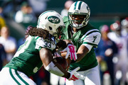 Geno Smith #7 of the New York Jets hands off to teammate Chris Ivory #33 in the first quarter during a game against the Denver Broncos at MetLife Stadium on October 12, 2014 in East Rutherford, New Jersey.